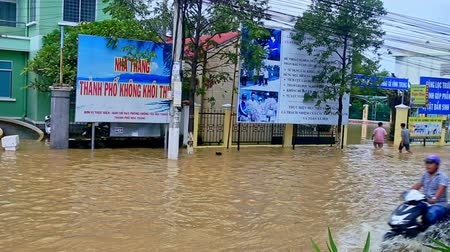 floods : NHA TRANG  VIETNAM - OCTOBER 21 2016: Heavy flood in city street became river house ground floor in water guys on October 21 in Nha Trang
