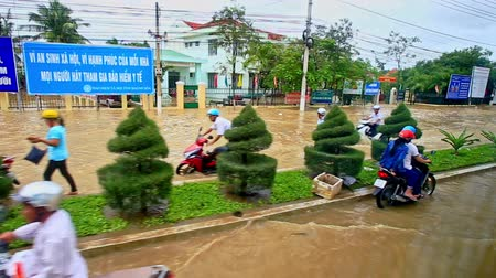 difficults : NHA TRANG  VIETNAM - OCTOBER 21 2016: Heavy flood in city street became a river car lorry wheels drive in water people draw scooters in Vietnam on October 21 in Nha Trang Stock Footage