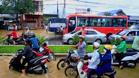 floods : NHA TRANG  VIETNAM - OCTOBER 21 2016: Heavy flood in city street became river lorry scooters bus cars traffic jam water tide wave rolls along road on October 21 in Nha Trang