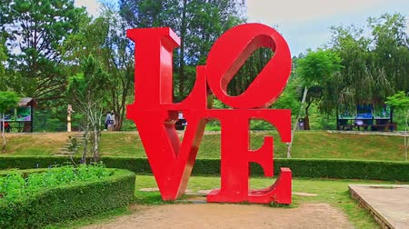 installation lectrique : closeup large red letters sculpture LOVE against grass lawn in tropical park