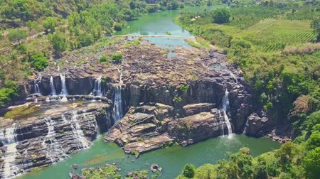 agua : drone shows amazing view of wide river rapids waterfalls Pongour from steep high cliff against green jungle and highlands