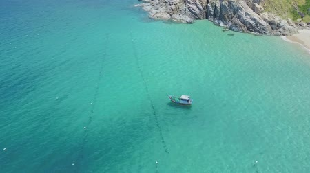 sand lia : Aerial view blue boat sails on shallow turquoise ocean by rocky hill and sand beach under scorching sun Stock Footage