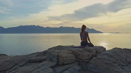 pigtailler : Drone backside view girl with pigtail stand to yoga pose Bridge on rock against sunrise above ocean