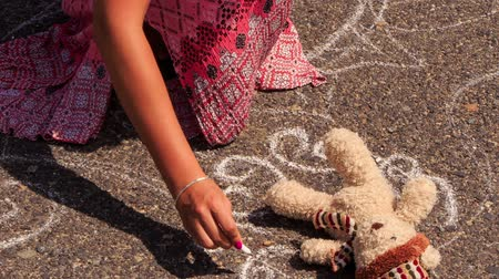 мел : Closeup girl in long dress squats and draws with a piece of chalk on asphalt pavement around small toy bear