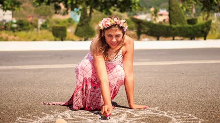 мел : Young blond woman in artificial flower garland squats and draws with a piece of chalk on asphalt pavement Стоковые видеозаписи