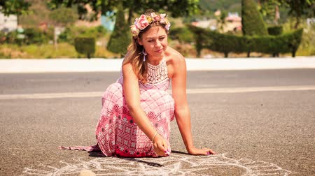 мел : young blond girl in artificial flower garland and long dress squats draws with chalk on asphalt pavement Стоковые видеозаписи