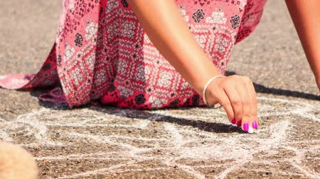 мел : closeup young woman in pink long dress and garland squats draws lines with piece of chalk on asphalt pavement Стоковые видеозаписи