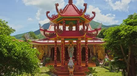 pielgrzymka : drone moves to religious red roof pagoda pavilion with sculptures in temple courtyard against green hills and blue sky