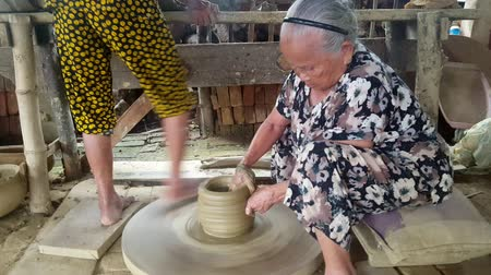 terracota : HOI AN  VIETNAM - OCTOBER 15 2017: Closeup of old asian women make earthenware crockery by ancient way Stock Footage