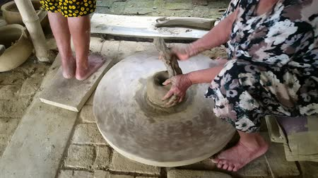 terrakotta : HOI AN  VIETNAM - OCTOBER 15 2017: Closeup grey-haired old woman takes clay roll and forms earthenware crockery large pot on special wooden wheel on October 15 in Hoi An