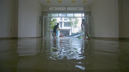 floods : NHATRANG  VIETNAM - NOVEMBER 04 2017: Woman man clear out of flood water on the floor with brooms as after the heavy rain during devastating typhoon on November 04 in NhaTrang
