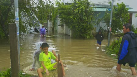 floods : NHATRANG  VIETNAM - NOVEMBER 04 2017: Young boys play fool swimming on thick plank along flooded street after destructive typhoon on November 04 in NhaTrang Stock Footage