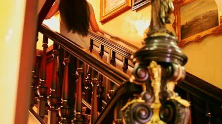 luxuriantly : backside brunette girl with long hair goes up quickly upstairs in nice decorated hallway with pictures Stock Footage