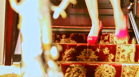 luxuriantly : slim girl in red shoes and purple dress steps down beautiful staircase in old rich style in hallway