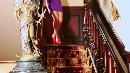 luxuriantly : tall woman in purple dress goes down carpeted wooden staircase with golden angel sculpture in hallway Stock Footage