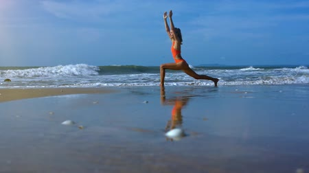 harcos : side view young athletic woman in orange swimsuit makes yoga warrior pose on beach against ocean