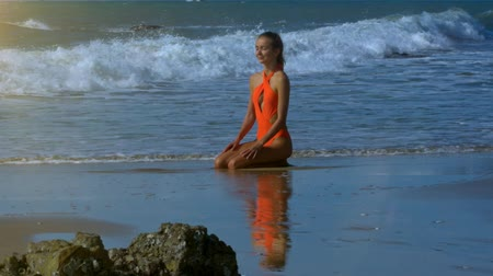 waterline : happy attractive girl in orange bikini sits and relaxes on ocean foamy waterline with stones on foreground