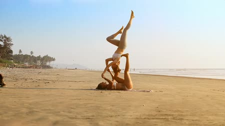 difficults : GOA, INDIA  INDIA - DECEMBER 09 2012: Strong girls perform stunning couple yoga pose on wet pressed ocean beach sand on tropical plants under sunlight on December 09 in Goa