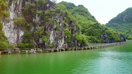 halong : flycam moves to blond long haired girl walking on a wooden bridge crossing tranquil bay along green islands in Ha Long bay