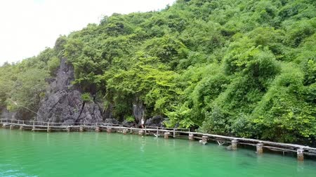 halong : flycam removes from a woman walking along a narrow bridge spread above tranquil sea near hilly islands Stock Footage