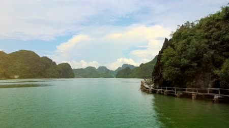 halong : drone follows woman walking along a low wooden bridge near a tropical island in natural miracle Ha Long bay