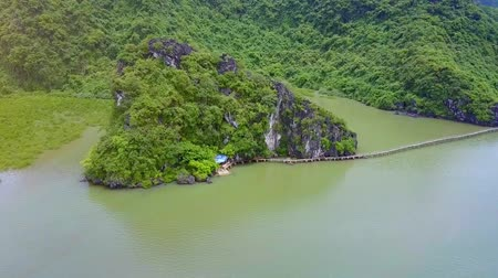 halong : drone approaches small green island located in calm sea and wooden bridge connecting two coasts