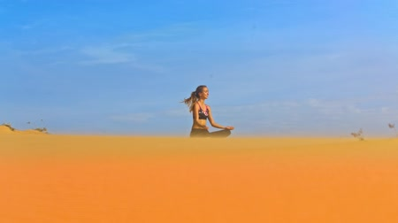 pozíció : amazing view from below wind shakes blond long hair of a young girl sitting in lotus pose on golden sand against blue sky