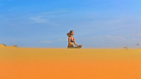 aşağıda : amazing view blonde long haired girl sits in yoga lotus position between golden sand and boundless blue sky Stok Video