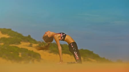 kumul : closeup view view slim girl sits in yoga pose Ustrasana in breeze among endless golden dune
