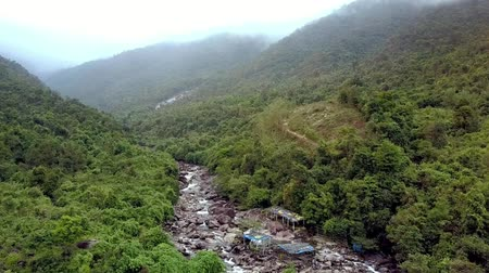 montanhoso : flycam moves close to the mountain river with cemetery graves on rocks on forestry banks against hilly jungle