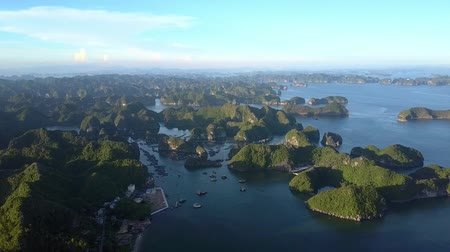 halong : upper panoramic view famous ocean bay with small rocky islands in natural zone and large island with town and sunset sky