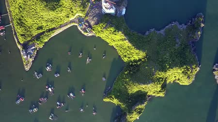 halong : drone rotates above green island with sunset sunny and shady hills and fishing boats in pictorial ocean bay