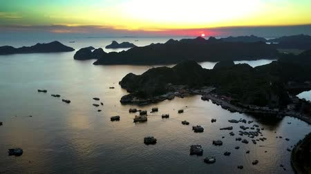 halong : drone rises above floating houses and boats in bay by island and sun
