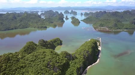 halong : drone moves above green hilly island with asphalt road at the hillside among the pictorial tranquil ocean bay