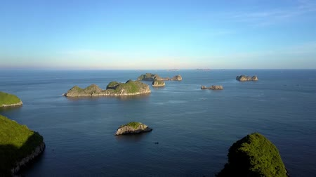 halong : drone moves slowly above wonderful tranquil azure bay with small rocky islands against beautiful sky
