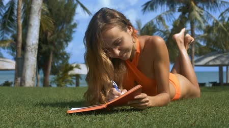 lírios : close view blonde lady with long hair in orange swimsuit sunburns on grass in diary against beach umbrellas