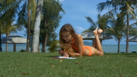 çim : beautiful slim blond girl in bright orange swimsuit lying on green grass and reads book against palm trees and sky