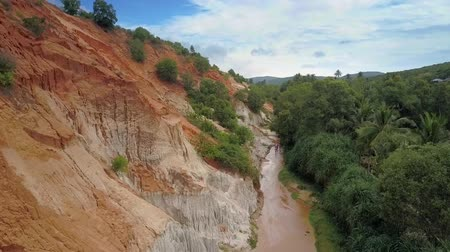 lírios : amazing aerial view ancient canyon with narrow river and high sandstone cliffs colored with clay against tropical forest Stock Footage