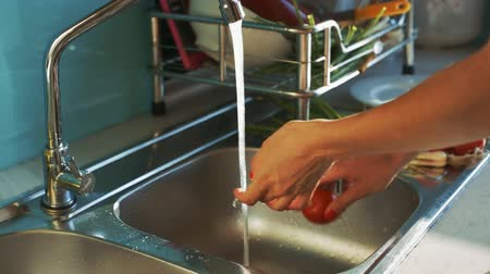 ripen : closeup girl washes red ripen tomatoes under water stream over sink and puts on plate in kitchen Stock Footage