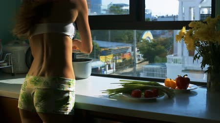 ripen : backside girl silhouette in shorts cuts tomatoes with knife on board