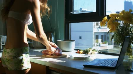 глыба : side view young slim housewife cuts fresh red meat lump to slices and notebook on table in kitchen