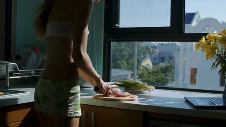 white onion : long haired girl silhouette cuts meat on pieces on white kitchen table with yellow flowers in front of window