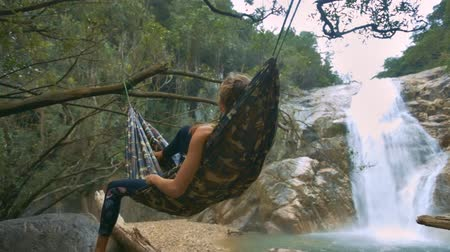 bum : closeup backside view girl figure relaxes lying in hammock bound between trees against pictorial waterfall Stock Footage