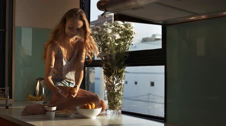 shake hair : wind shakes girl long loose flowing hair she sits and peels tangerines on windowsill like table with white flowers Stock Footage