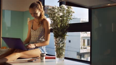 chryzantema : beautiful blond lady with ponytail sitting on wide windowsill near chrysanthemums in vase closes laptop and dreams