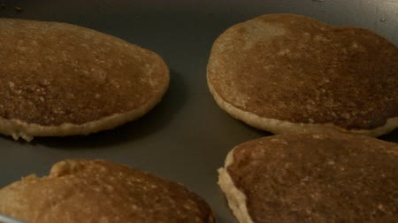 zab : closeup tasty delicious gold round soft oat pancakes fried on modern black pan in light kitchen Stock mozgókép