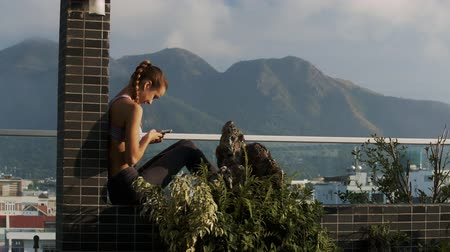 veranda : pretty girl with long ponytail plait reads sms in phone sitting on rooftop