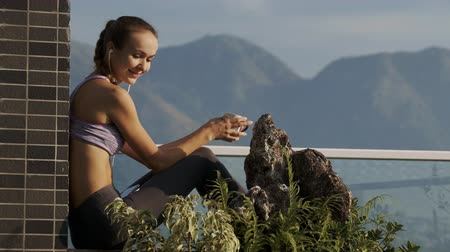 veranda : close-up picture girl listens to music holds coffee cup resting on rooftop terrace near plants and decorative stones