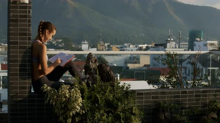 впечатляющий : closeup side view young girl reading books sitting on rest terrace against impressive hills rising above city