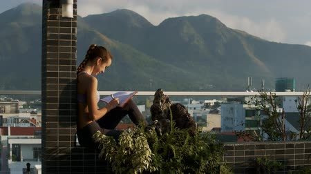 veranda : closeup side view woman with plait sits on the terrace and writes down thoughts in diary against amazing landscape